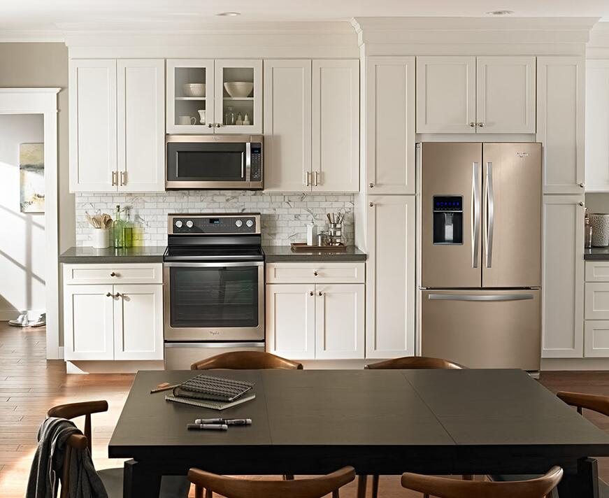 Whirlpool Sunset Bronze kitchen appliances with white cabinetry in a contemporary kitchen.