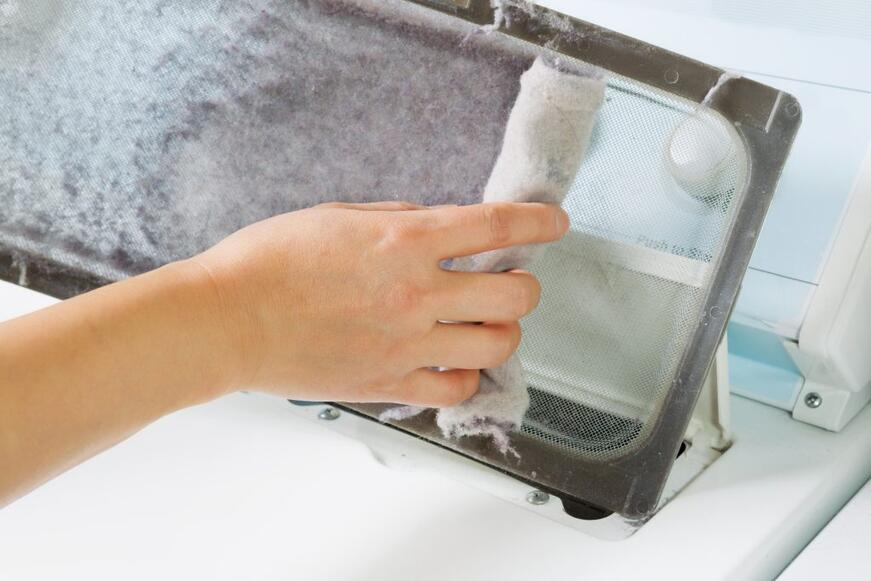 Horizontal photo of female hand taking the lent out from dirty air filter of the clothing dryer.